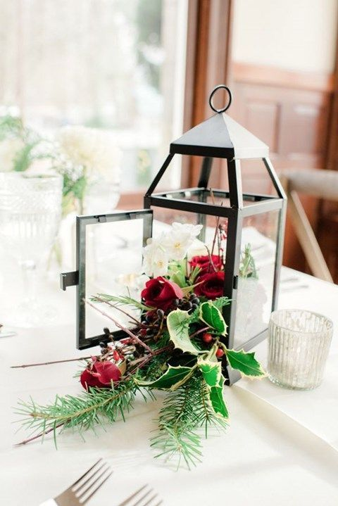 a Christmas centerpiece of a lantern and holly leaves and berries, white and red blooms and evergreens