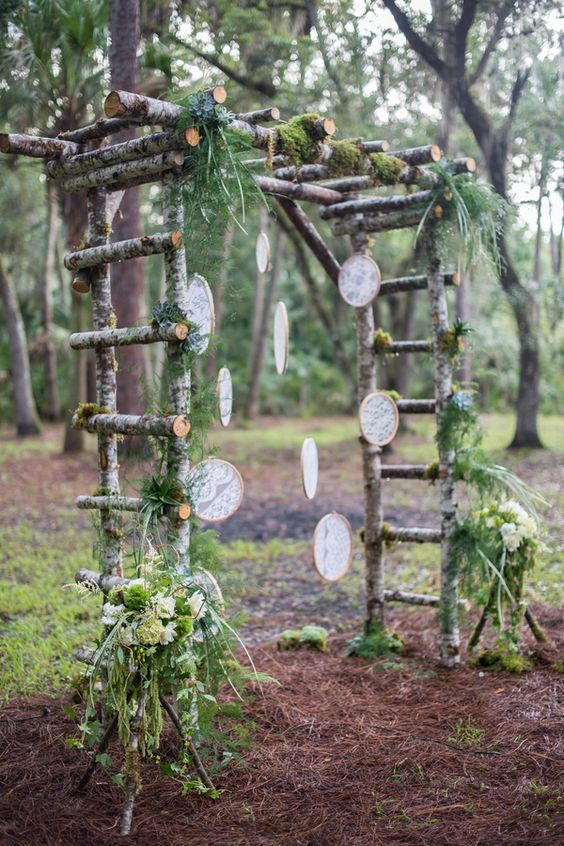 a birch branch arch with greenery and lace dream catchers fits a boho woodland wedding