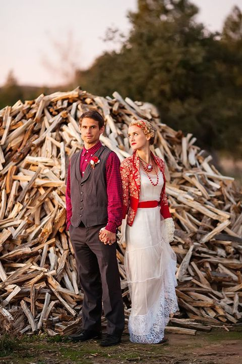 a bride wearing a vintage-inspired wedding gown with a red sash and a printed red cardigan, a groom wearing a grey suit and a plaid shirt