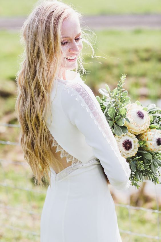 a modern plain wedding dress with long sleeves and a cutout back with lace trimming and lace inserts on the sleeves