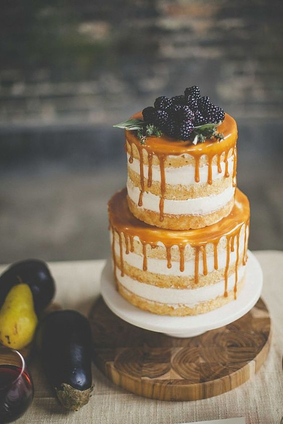 a naked fall wedding cake with caramel dripping, greenery and blackberries on top will be a great idea for the fall