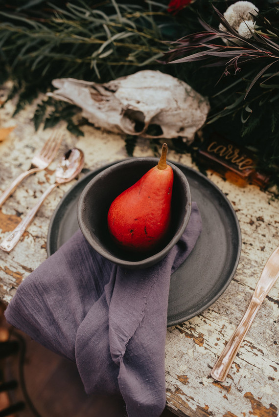 Each place setting was done with matte grey plates and bowls, a red pear and a graphite grey napkin