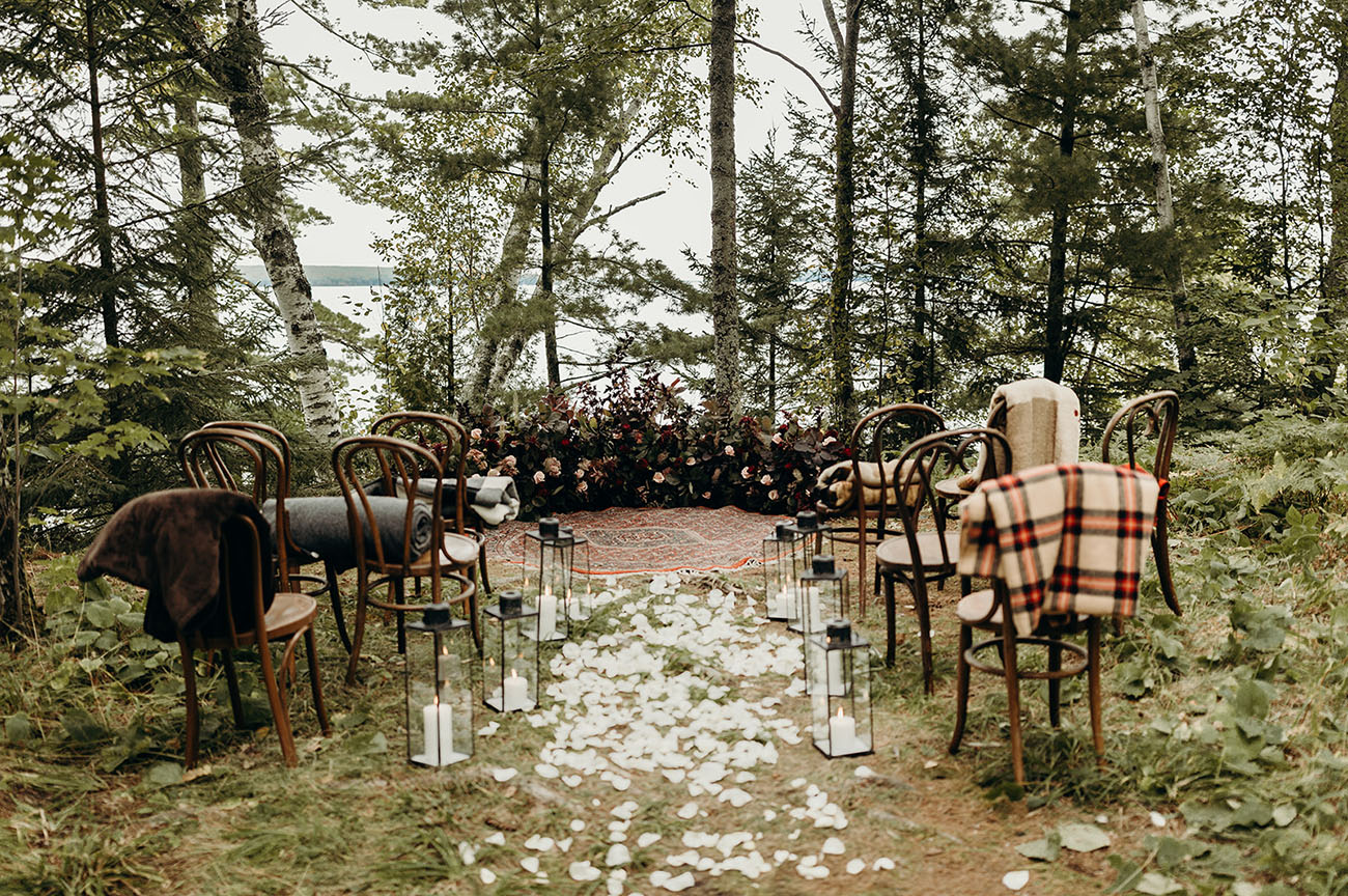 The ceremony space was done with a lush moody floral semi circular arch and a boho rug, with lanterns and petals
