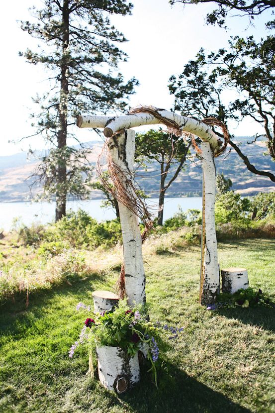a birch branch wedding arch with vine, logs and flowers around is a simple and cool idea for a spring Scandinavian wedding