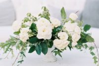 06 a chic wedding centerpiece with lush greenery and white blooms is classics