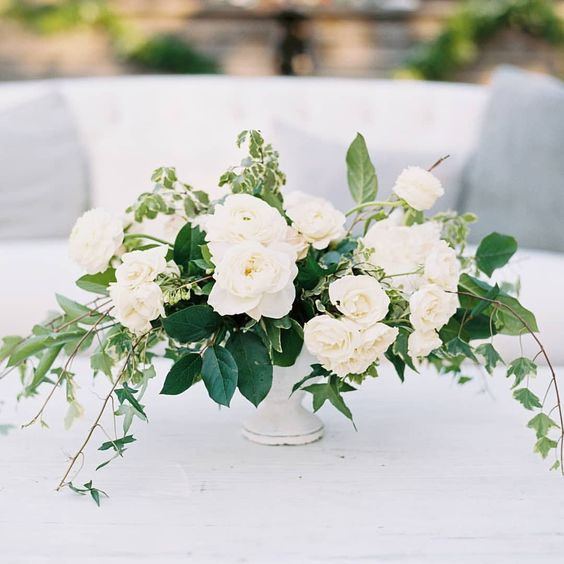 a chic wedding centerpiece with lush greenery and white blooms is classics