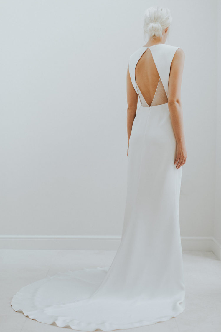 a minimalist wedding dress with a cutout geometric back and sheer detailing plus a train for a minimal bride