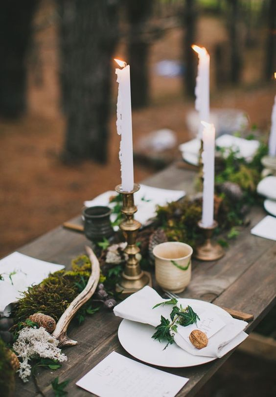 a moss runner, white moss, antlers, pinecones and tall candles are amazing for a woodland wedding centerpiece