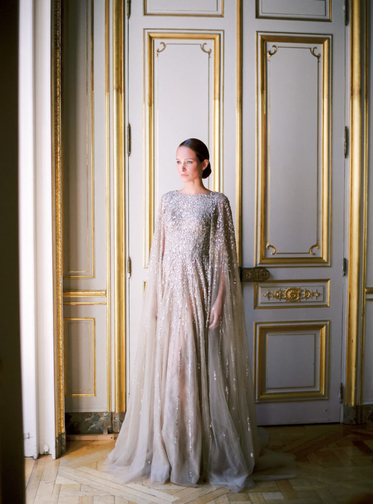 a silver grey wedding dress with heavy embellishments and a matching cape for a fashion-forward bride