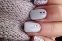 06 glitter and white nails with two rhinestones on each for a sparkly and glam holiday look