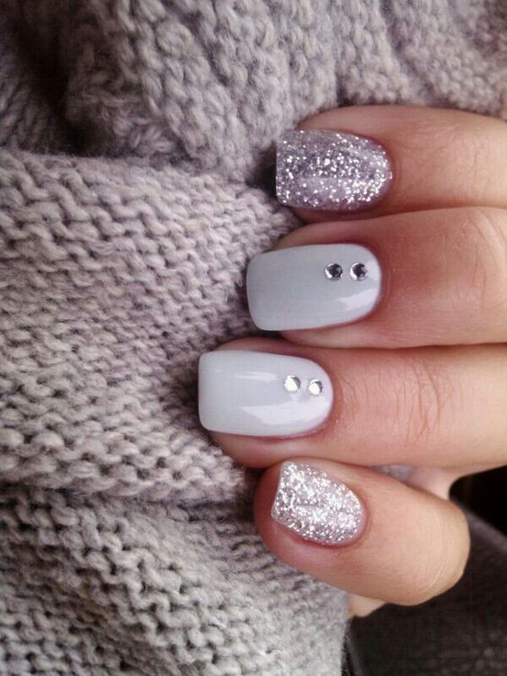 glitter and white nails with two rhinestones on each for a sparkly and glam holiday look