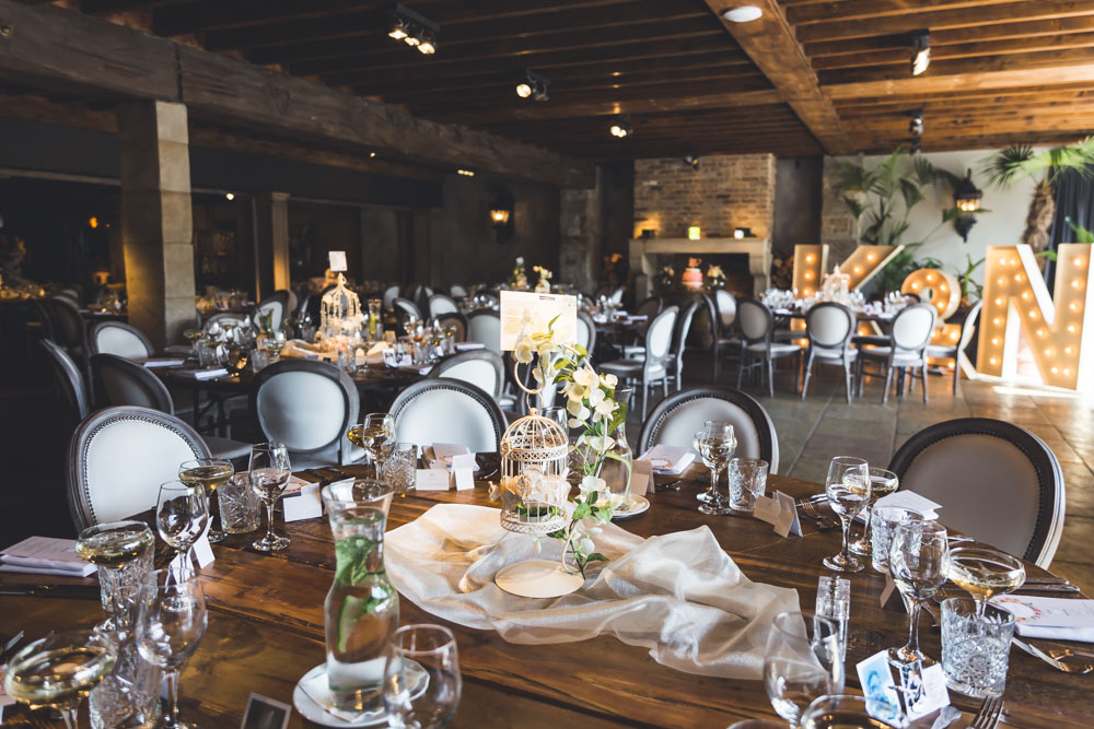 The venue was styled with cute bird cage and flower centerpieces for a breezy look