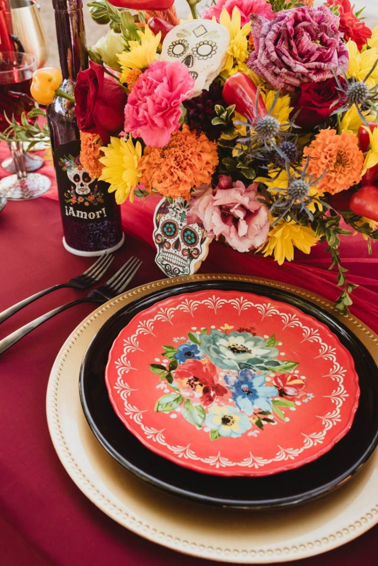 The wedding tablescape was done in black, red and gold, with sugar skulls, bright blooms