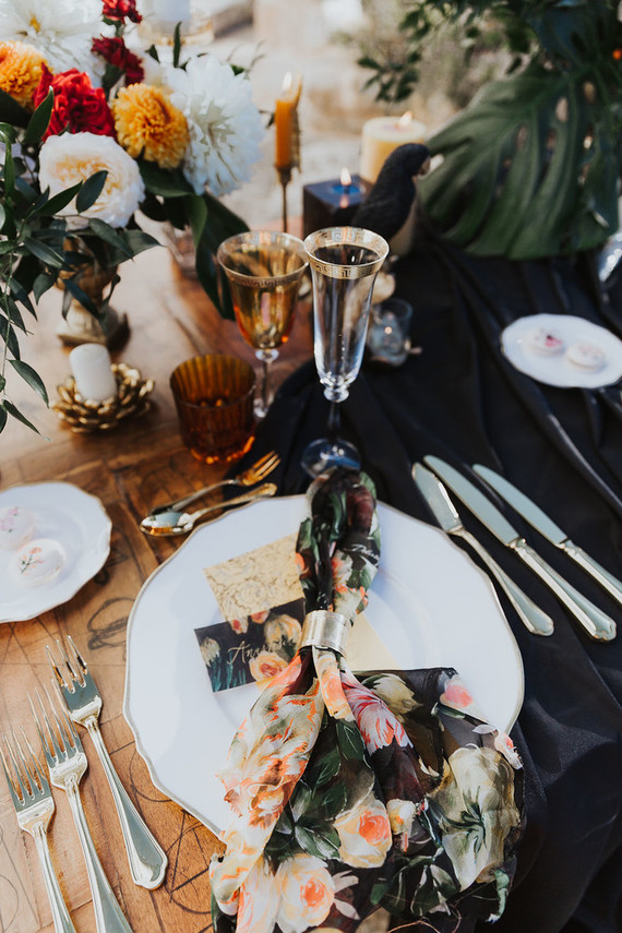 The wedding tablescape was done with moody table runners, gold rimmer glasses and floral fabric