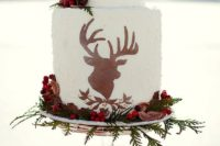 07 a Christmassy wedding cake with a deer silhouette, greenery, berries and nuts for a woodland wedding