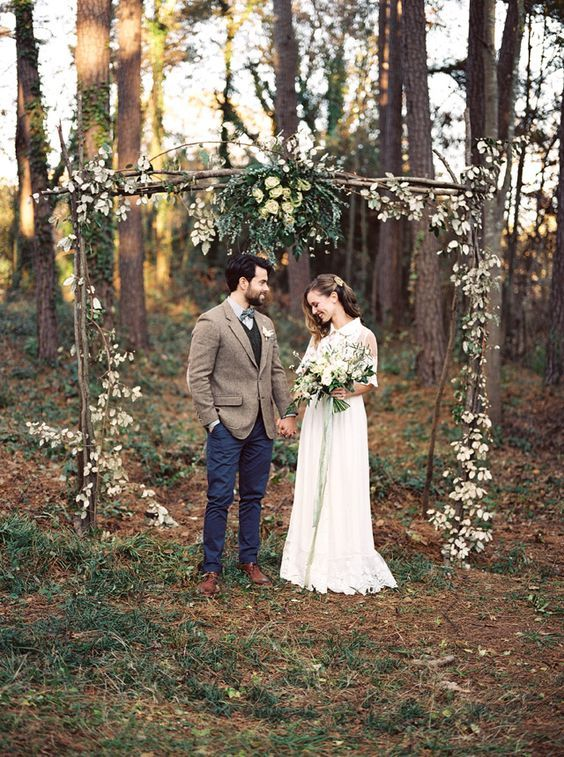 a boho branch wedding arch with greenery and leaves for a fall wedding with a retro feel