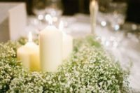 07 a classic centerpiece idea of candles and a lush wreath of baby's breath is ideal for a Christmas or winter wonderland wedding