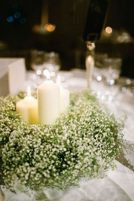 a classic centerpiece idea of candles and a lush wreath of baby's breath is ideal for a Christmas or winter wonderland wedding