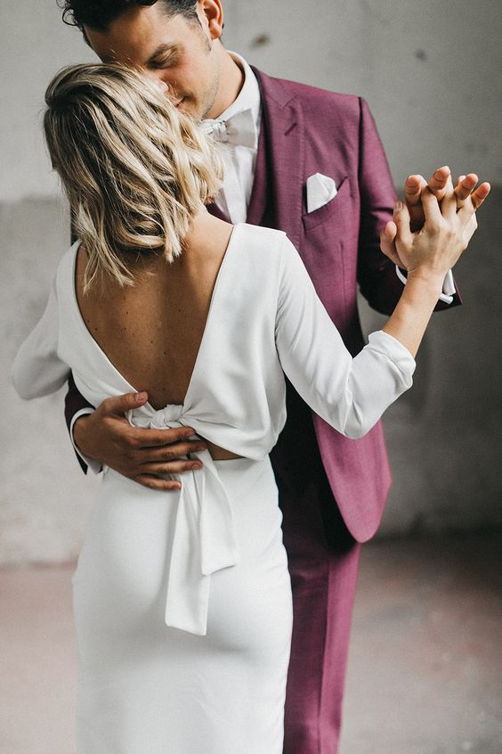 a modern plain fitting wedding dress with long sleeves and a tie back, midi length for a minimalist bride