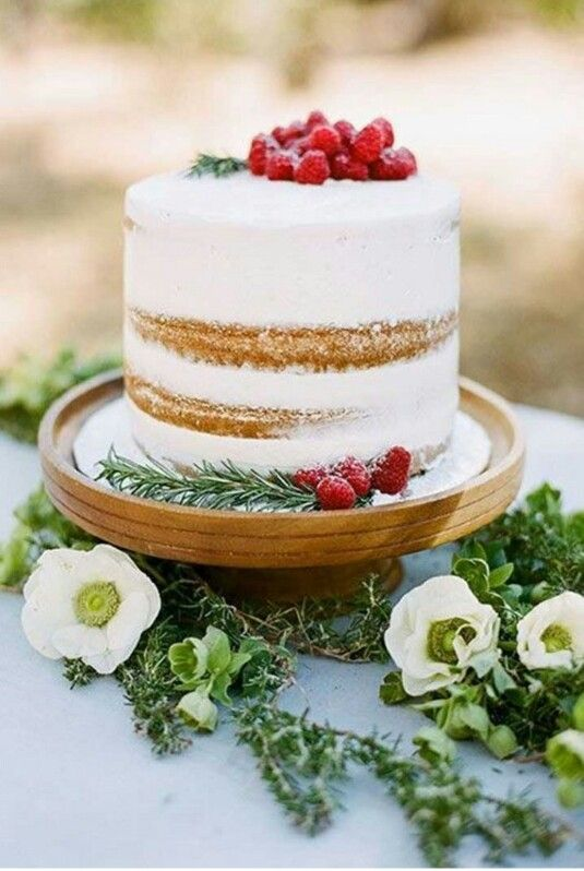 a naked wedding cake topped with rosemary and raspberries is amazing for Christmas