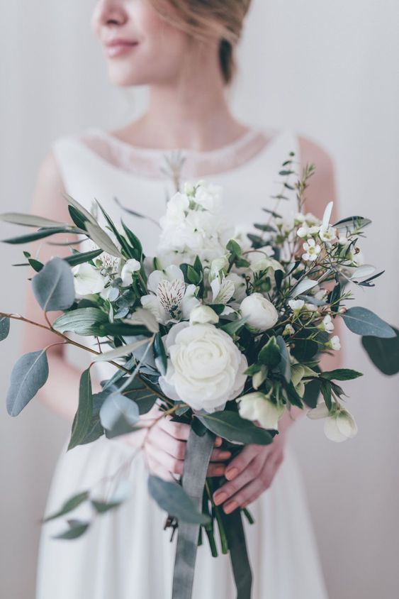 a refined and very textural wedding bouquet with foliage and white flowers plus dark ribbons