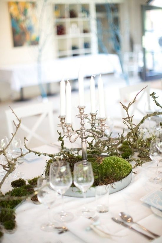 a simple and elegant Scandinavian wedding centerpiece of moss in a tin bowl, branches and a vintage candle holder