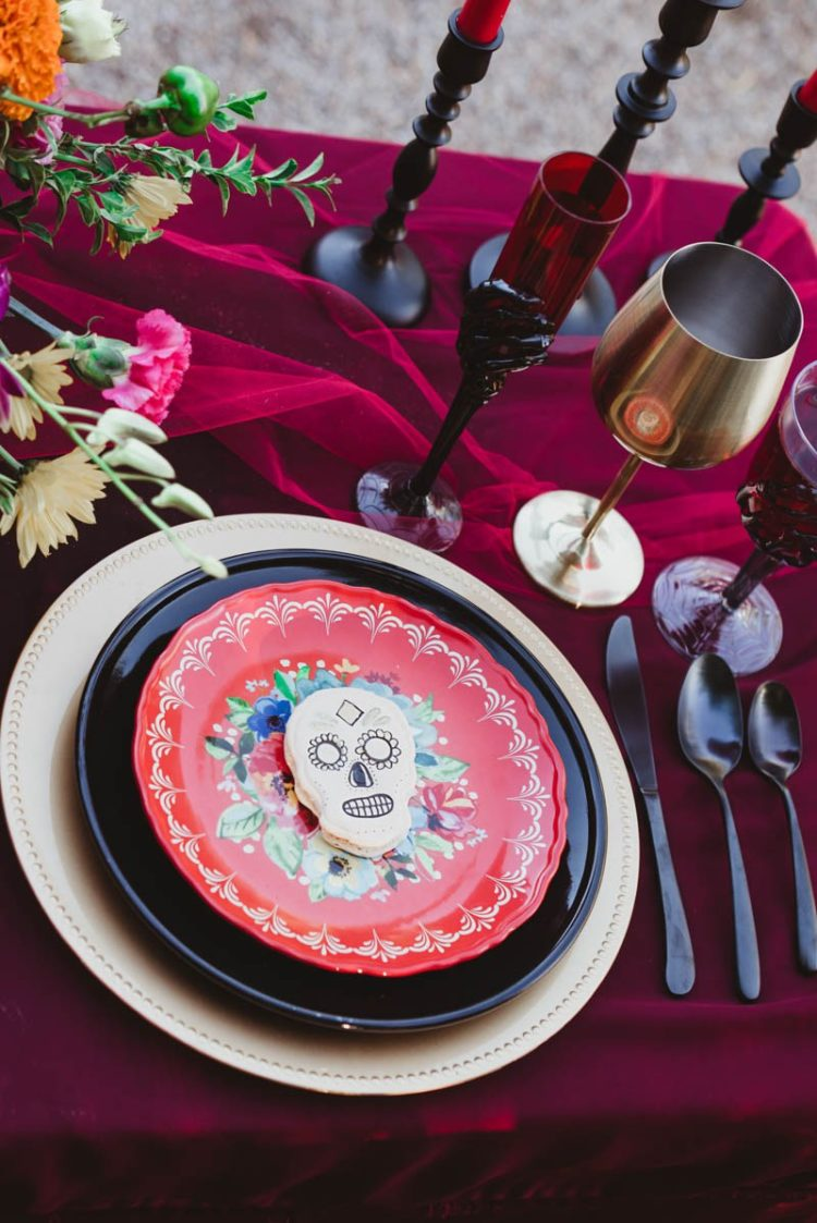 Colored glasses, dark cutlery and sugar skull cookies marked each place setting