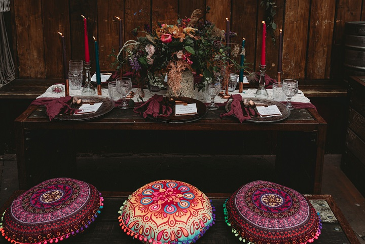 The wedding reception was styled as an indoor boho picnic, with a low uncovered table and Moroccan pillows as seats