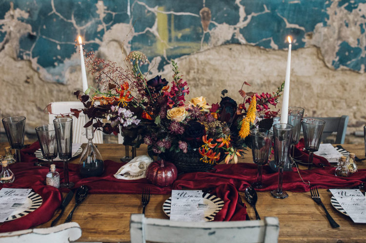 The wedding tablescape was done with a rich burgundy table runner, a fall centerpiece and dark glasses