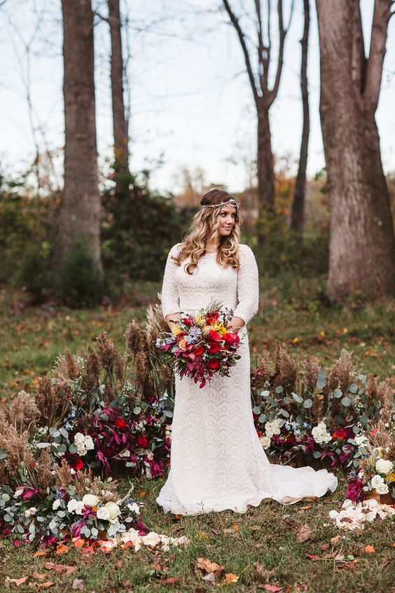 a boho fall semi-circular wedding altar done with dried herbs and rich-colored blooms plus foliage