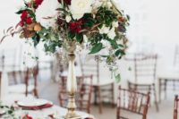 08 a lush Christmas centerpiece with a tall stand and blooms of white, red colors, greenery and berries