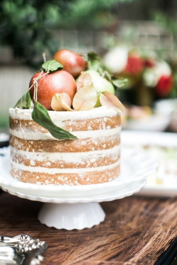 a naked wedding cake topped with apples is all you need for a Scandinavian fall wedding