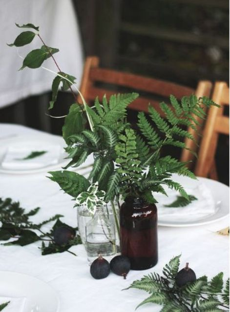 a simple centerpiece of pharmacy jars and greenery plus figs is great for a spring or summer woodland Scandi wedding