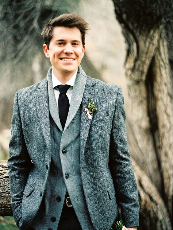 a winter groom look with a tweed jacket, a grey cardigan, a white shirt and a black tie for comfort and coziness