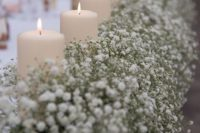 08 lush baby's breath table runner with candles is a chic idea for winter and other weddings