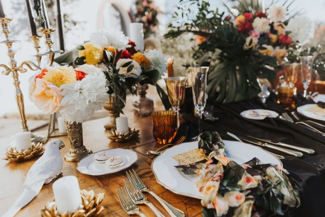 Fake birds, moody florals, colored glasses and candle holders brought a refined touch to the table setting