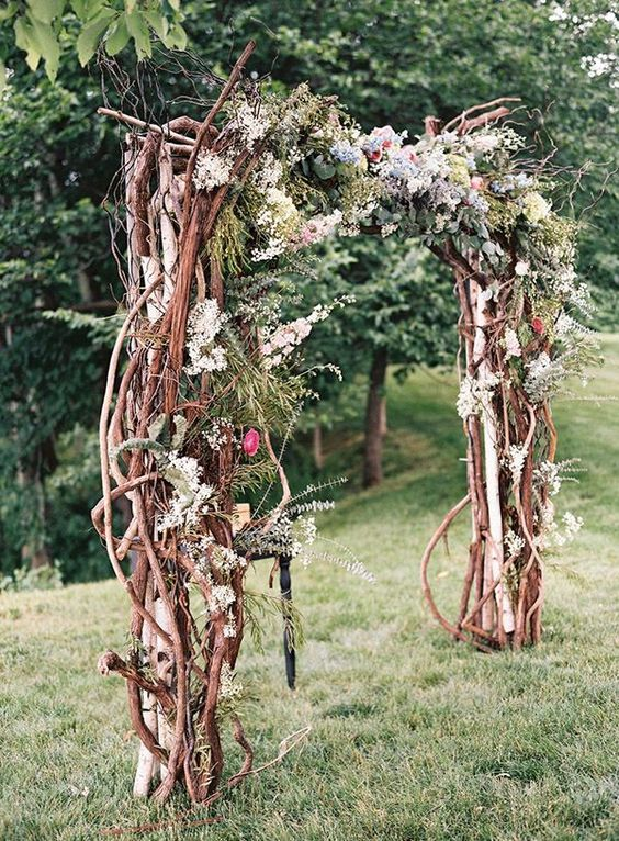 a boho woodland wedding arch of interwoven branches, moss, foliage, blooms and antlers for a summer or fall wedding