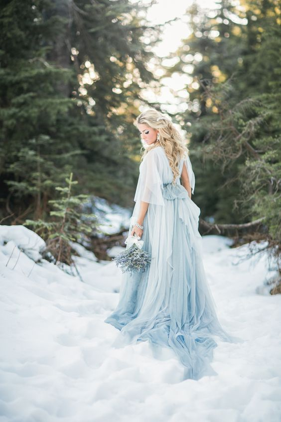 a layered airy powder blue wedding dress with short sleeves, a train and a cutout back
