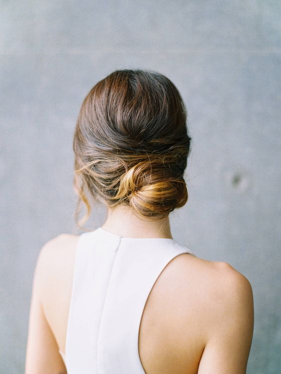 a modern low bun with a bump and locks down is a refined and elegant hairstyle for a minimalist bride