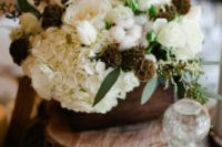 09 a rustic winter wedding centerpiece of wood slices, a wooden box, white blooms, cottons and herbs