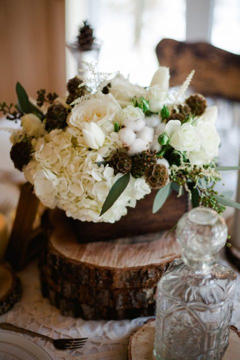 a rustic winter wedding centerpiece of wood slices, a wooden box, white blooms, cottons and herbs
