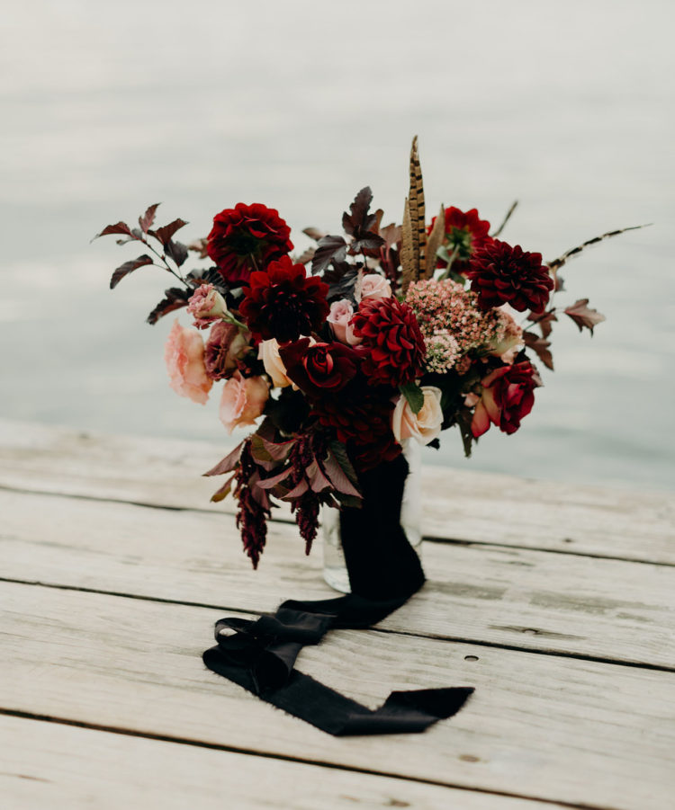 The wedding bouquet was a moody and lush one, with feathers and dark foliage plus black ribbons