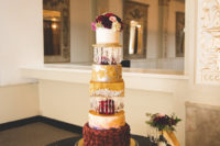 10 The wedding cake featured many parts in gold, burgundy and white, with fresh blooms and crystal pendants