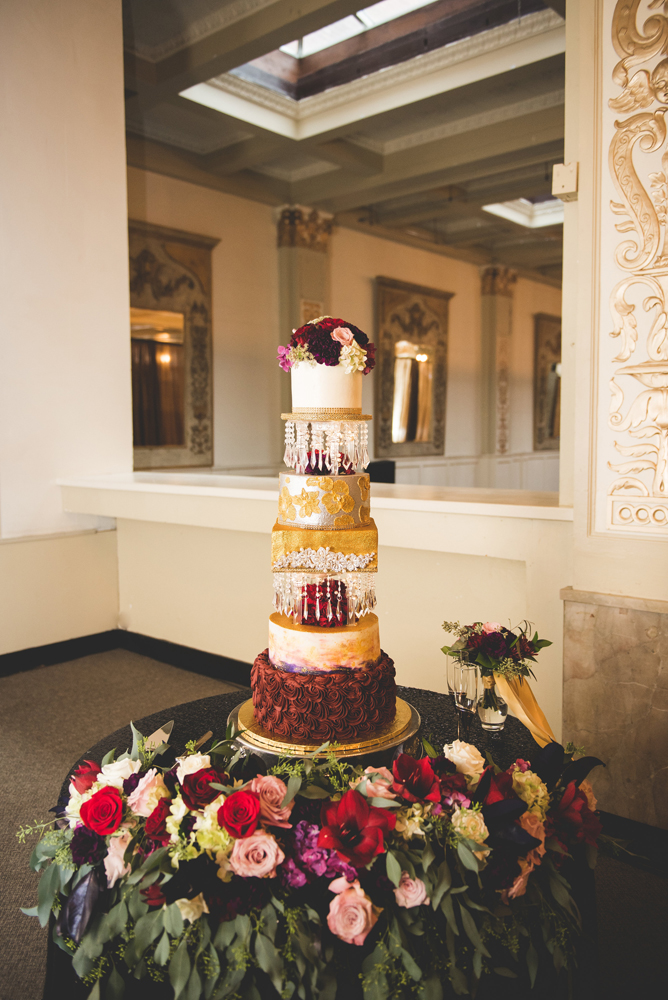 The wedding cake featured many parts in gold, burgundy and white, with fresh blooms and crystal pendants