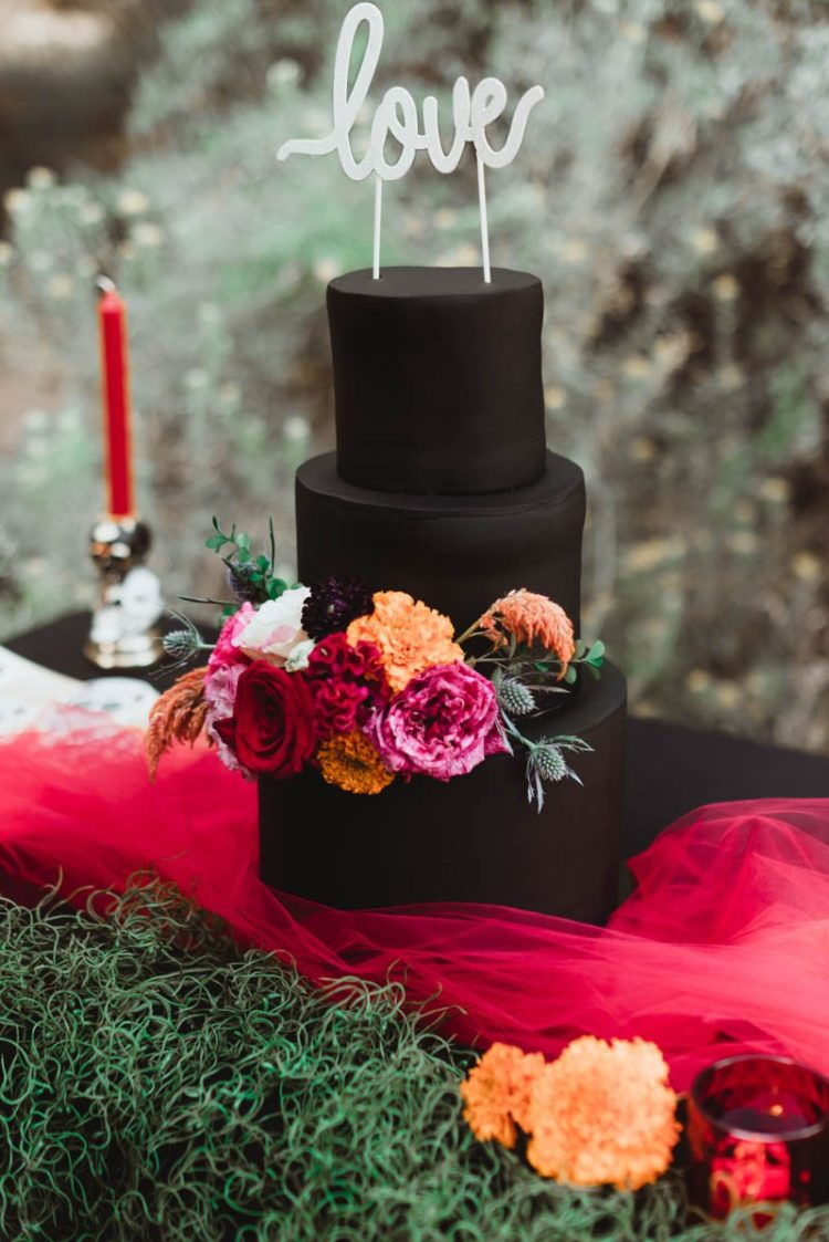 The wedding cake was a matte black one, with bold florals and styled with red tulle