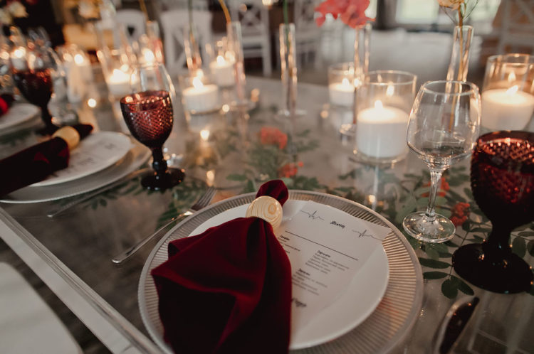 The wedding tables were styled with burgundy glasses and napkins, with candles and bright blooms