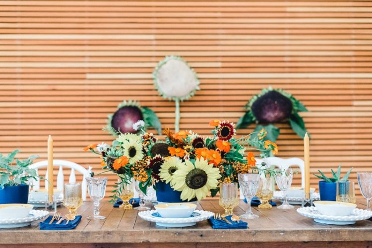 The wedding tablescape was a colorful one, with blue, red, ornage touches, colorful glasses and candles and potted cacti