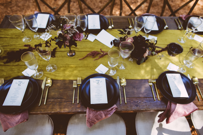 The wedding tablescapes were done with jewel-tone linens, black chargers and plates