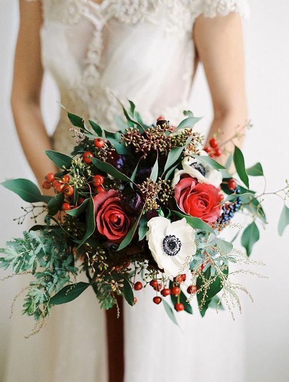 a bright wedding bouquet with touches of red, burgundy, with berries and foliage