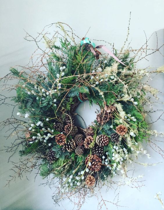 a cool winter wedding wreath with evergreens, pinecones, berries, twigs and ferns will be a nice venue decoration